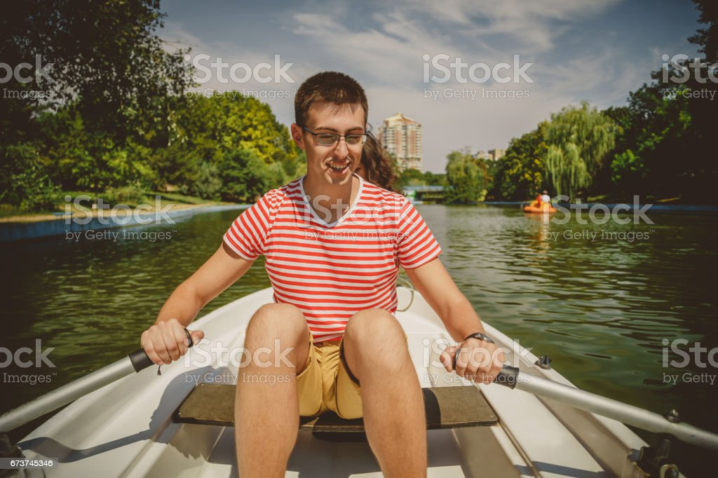 Young beautiful happy loving couple rowing a small boat on a lake. A fun date in nature. Couple in a boat. stock photo