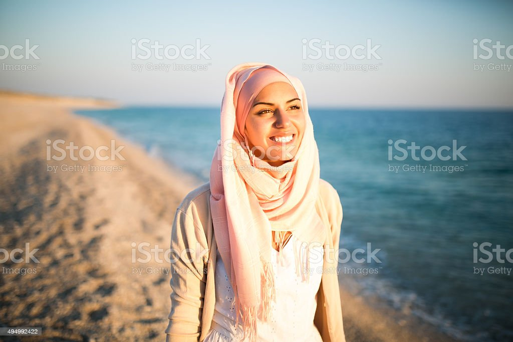 Young beautiful happy muslim woman on the beach stock photo