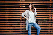 Young beautiful happy woman in casual cloths against wall
