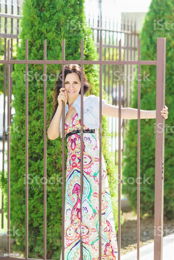 Young beautiful happy woman stands near the lattice fence stock photo