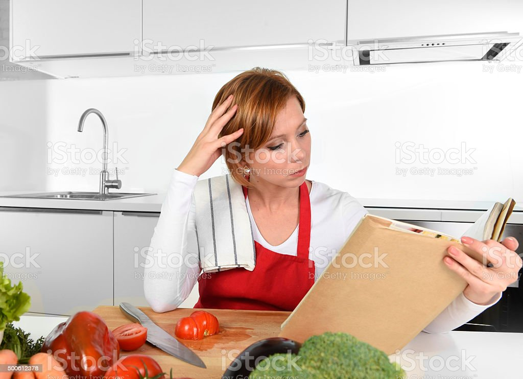 young beautiful home cook woman in kitchen reading cookbook stock photo