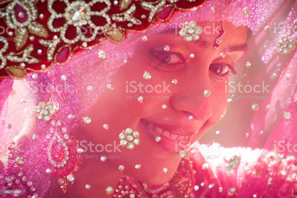 Young beautiful Indian bride looking through traditional veil stock photo