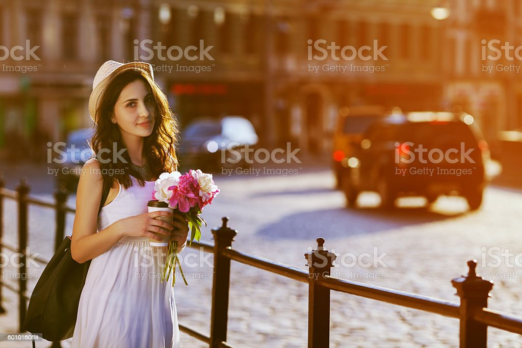 Young beautiful lady walking on street, holding paper cup with stock photo