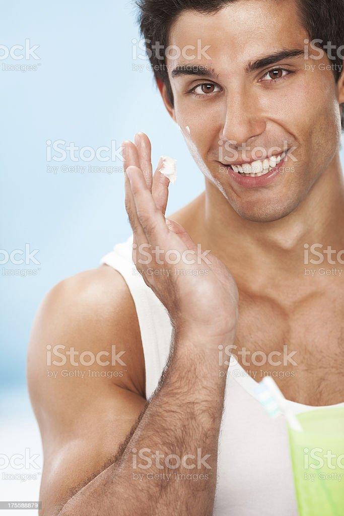 Young beautiful man applying cream royalty-free stock photo