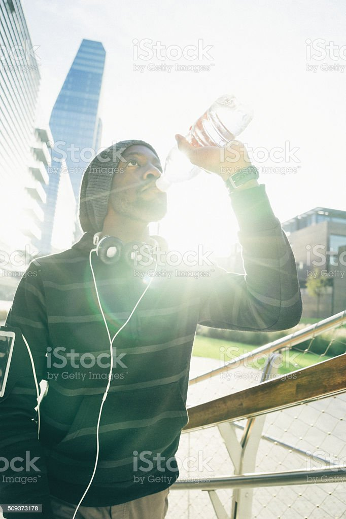 Young Beautiful Man Relaxing After Workout, Cityscape On Background stock photo