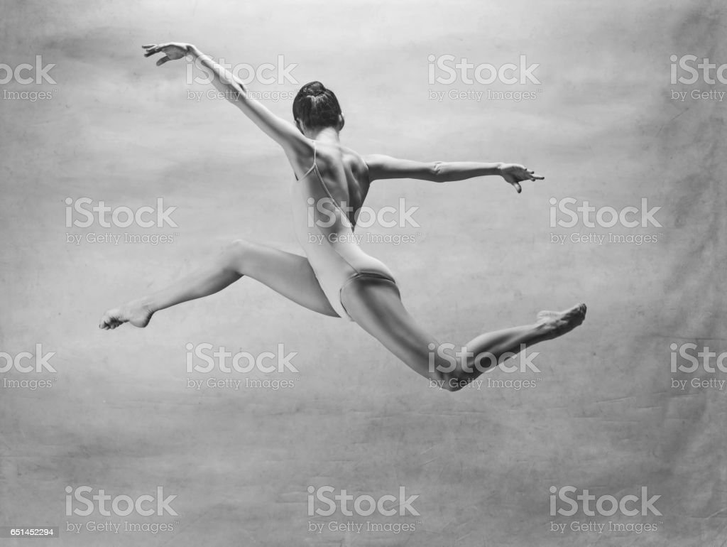 Young beautiful modern style dancer jumping on a studio background stock photo