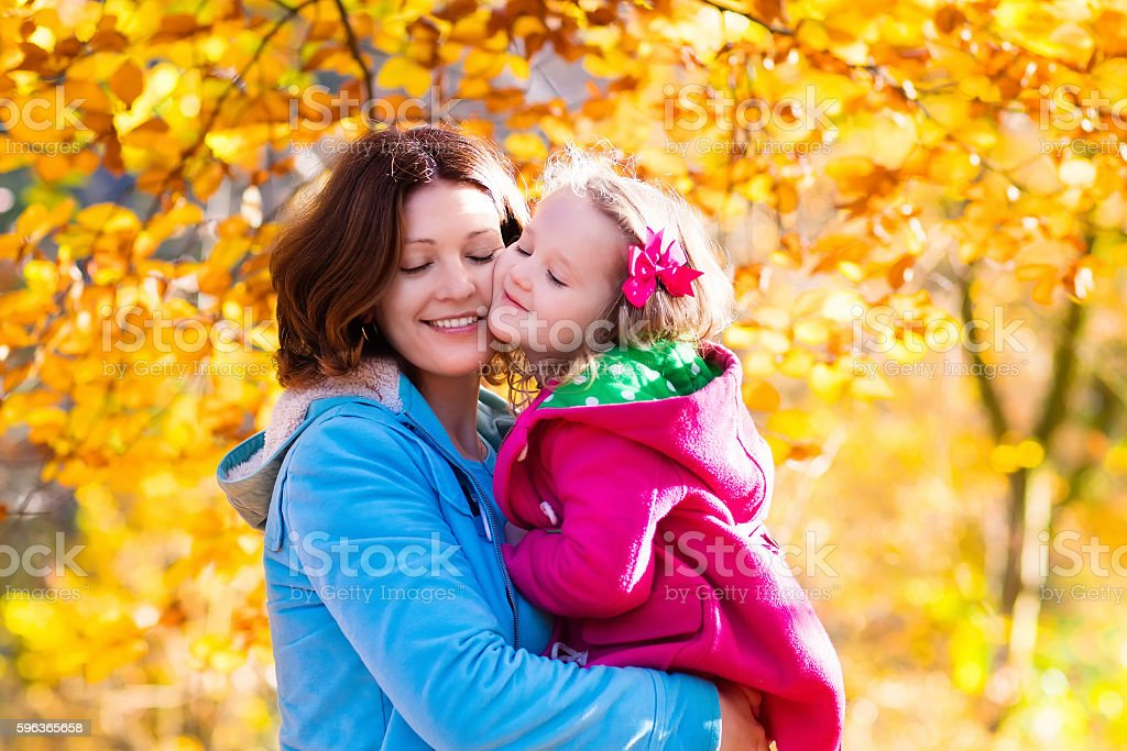 Young beautiful mother and child in autumn park stock photo