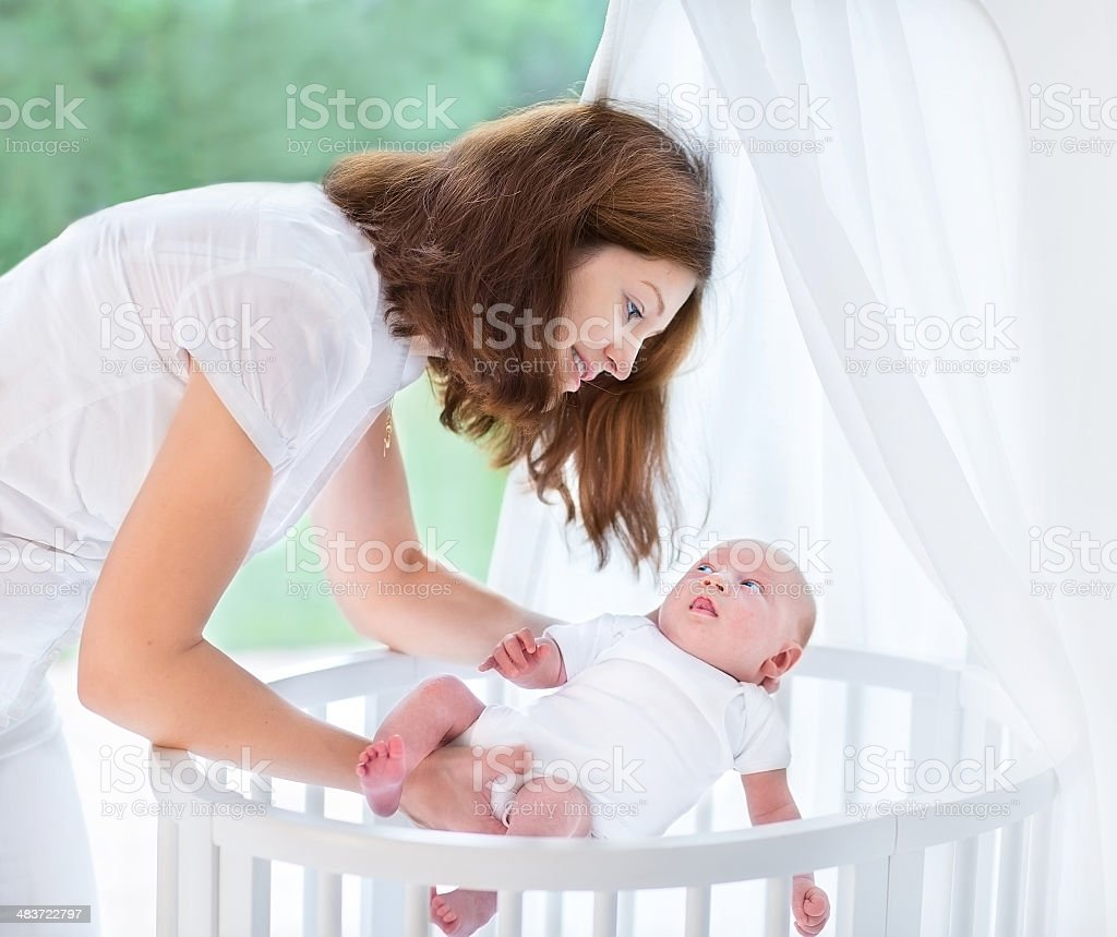 Young beautiful mother putting newborn baby into white round crib stock photo