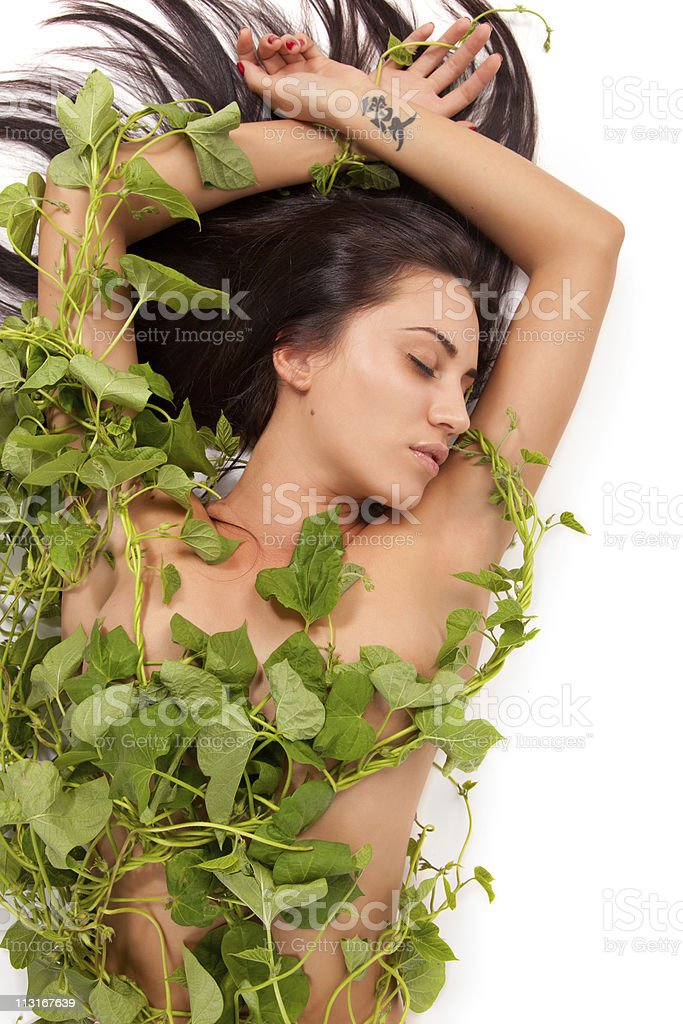 Young beautiful nude woman with green ivy leaves wrapped around stock photo
