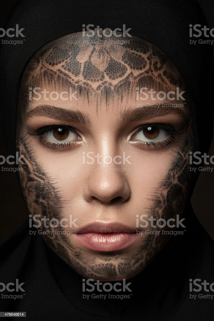 Young beautiful nun with faceart stock photo
