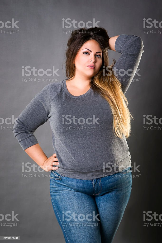 Young beautiful plus size model in blue jeans, xxl woman stock photo