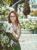 Young beautiful pretty woman with red hair and glasses posing