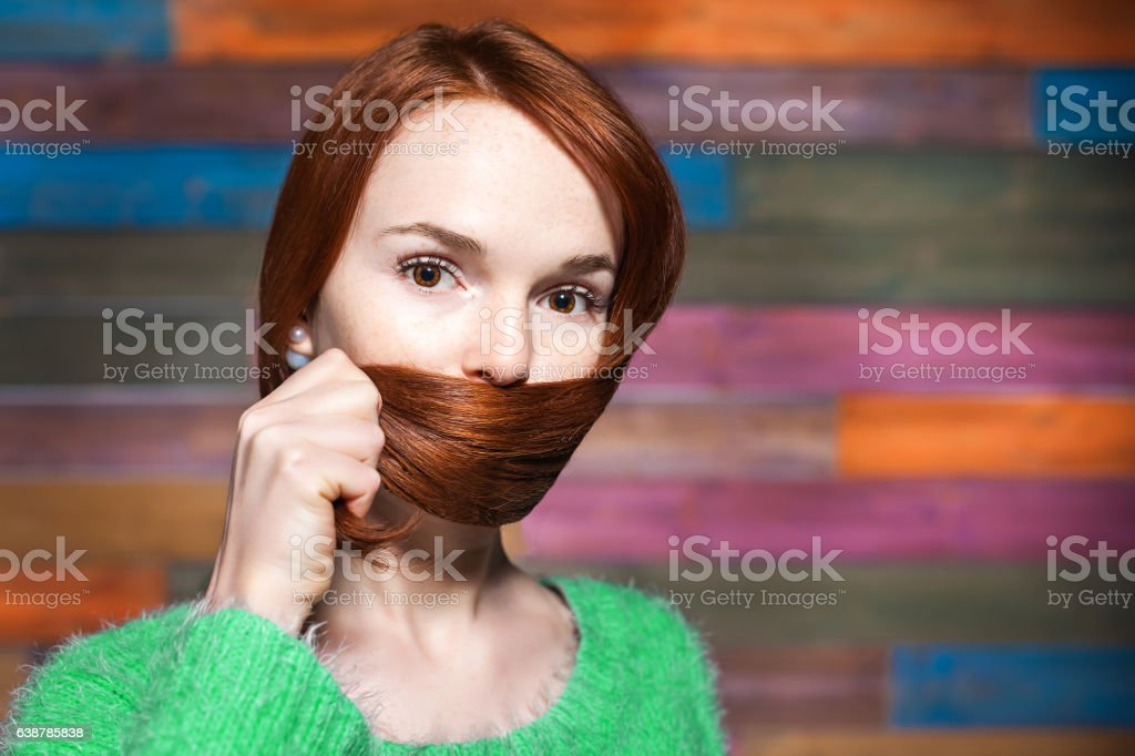 young beautiful red-haired girl covering mouth with her hair stock photo