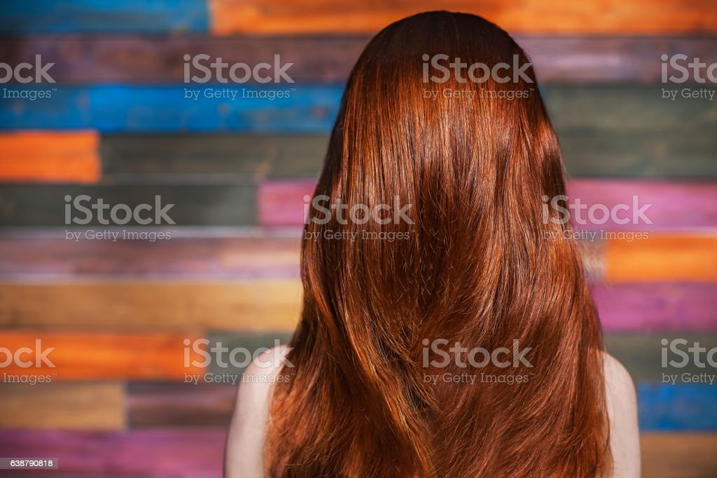 young beautiful red-haired girl standing back to the camera stock photo