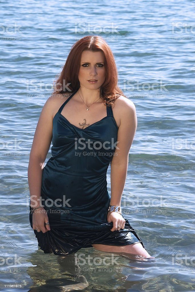 Young beautiful redhead dresssed up woman standing in the water royalty-free stock photo