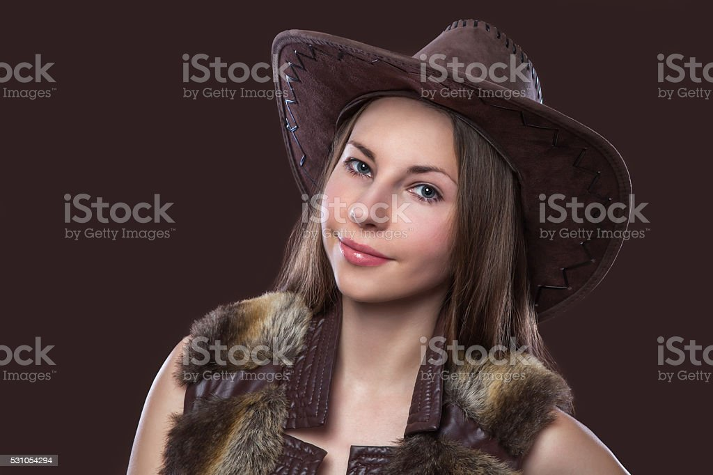 Young beautiful sexy girl in fur waistcoat and cowboy hat stock photo