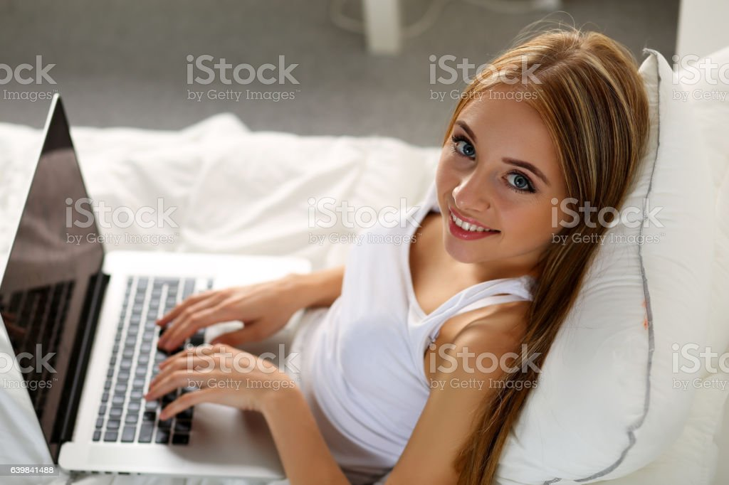 Young beautiful smiling blonde woman lying in bed stock photo