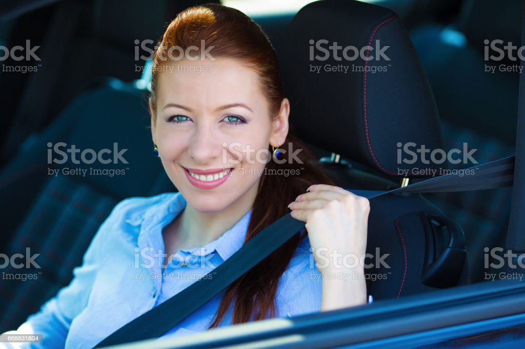 young, beautiful, smiling, happy, attractive woman pulling on seatbelt inside black car stock photo