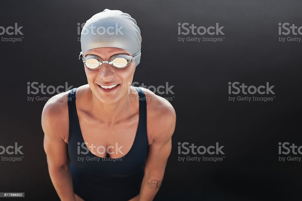Young beautiful sportswoman in swimsuit with swimming goggles stock photo