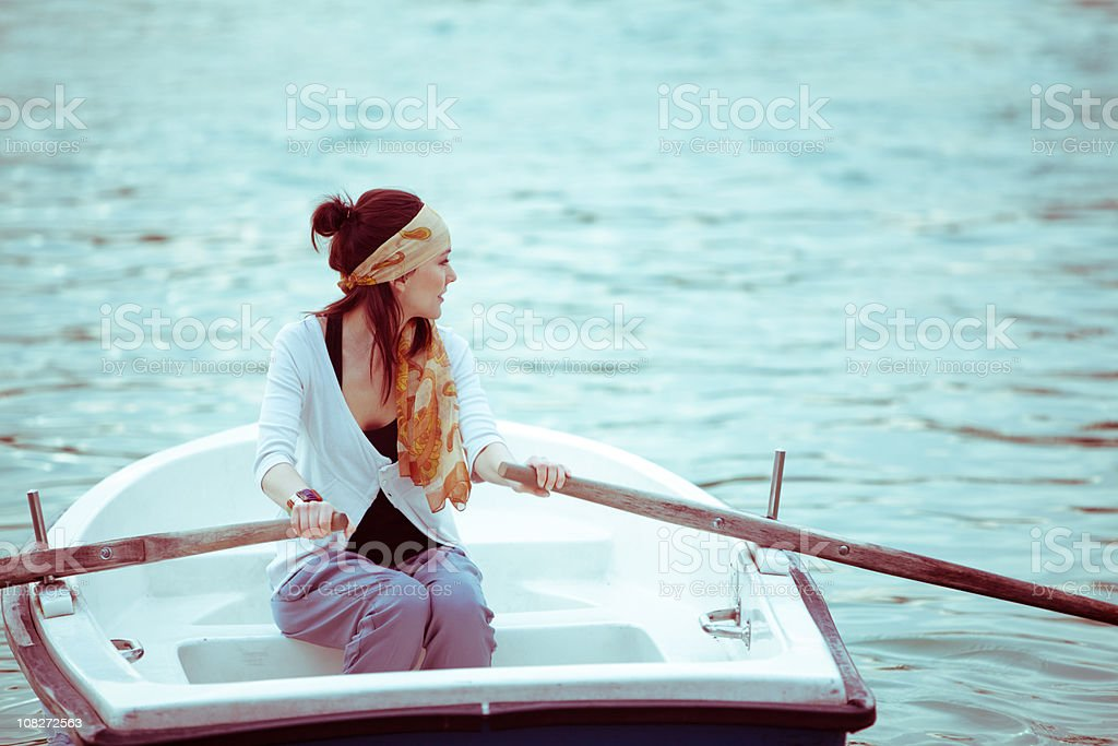 Young beautiful woman alone in a Rowboat royalty-free stock photo