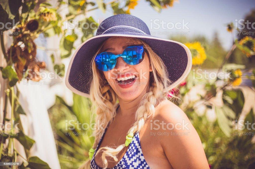 Young beautiful woman among blooming sunflowers stock photo