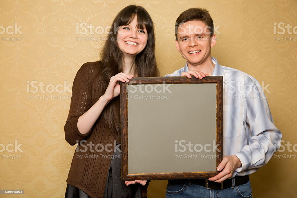 Young beautiful woman and smiling man with picture in hands royalty-free stock photo