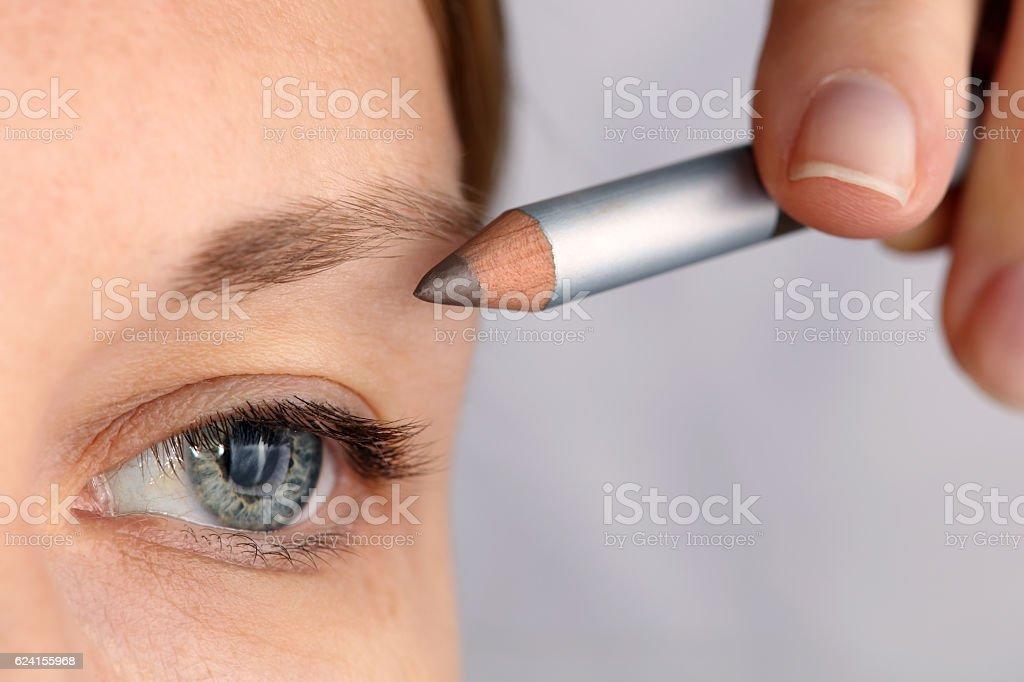 Young beautiful woman applying eyebrow pencil close up stock photo
