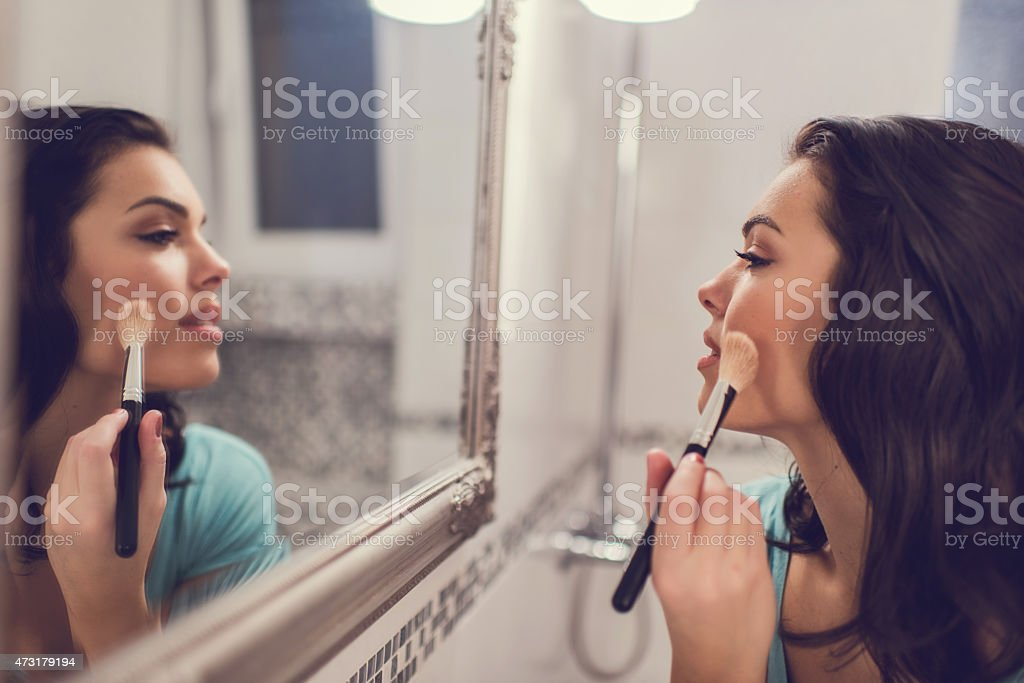 Young beautiful woman applying face powder in bathroom. stock photo