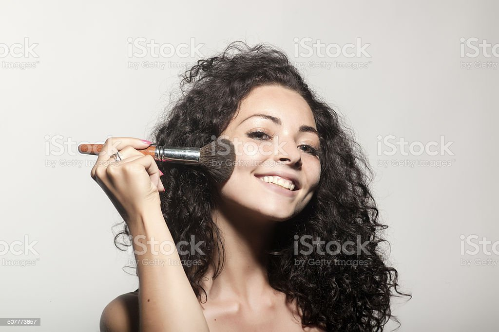 Young beautiful woman applying makeup on face by brush stock photo