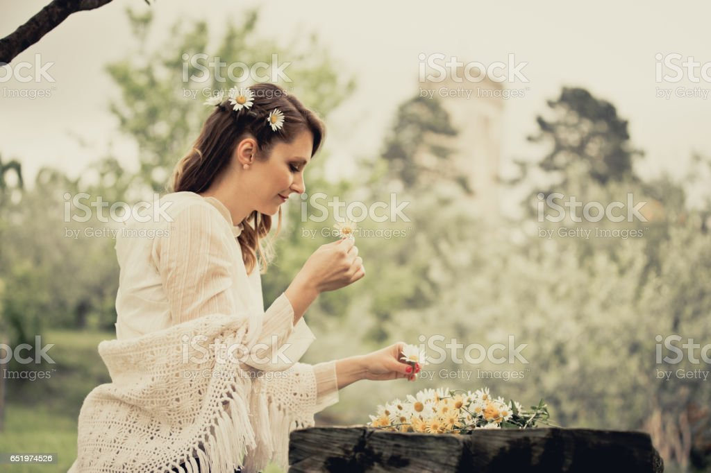 Young Beautiful Woman Arranging Flower In Her Hair stock photo