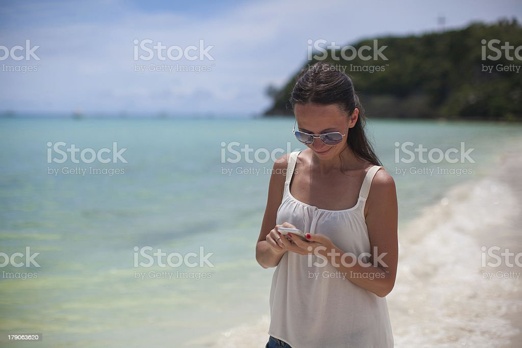 Young beautiful woman at the beach looking on her phone royalty-free stock photo