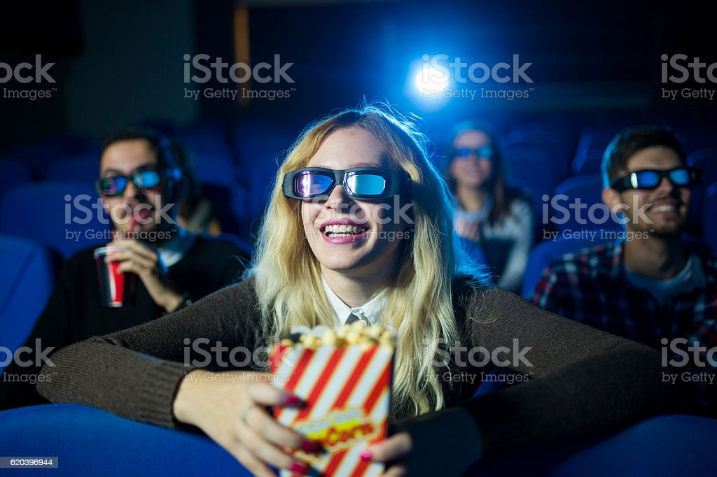 Young beautiful woman at the movies stock photo
