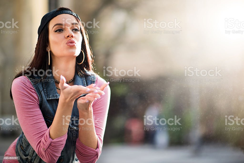 Young beautiful woman blowing a kiss to someone. stock photo