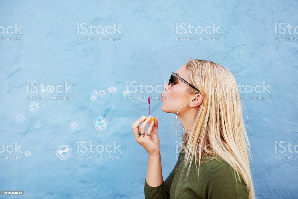 Young beautiful woman blowing soap bubbles stock photo