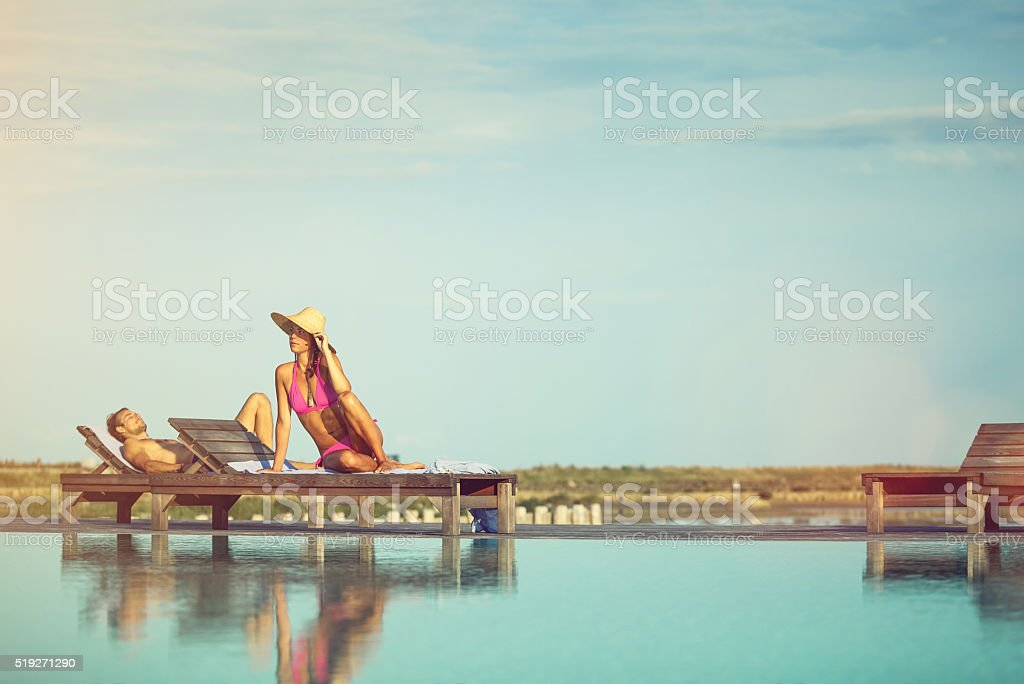 Young beautiful woman by the outdoor swimming pool stock photo