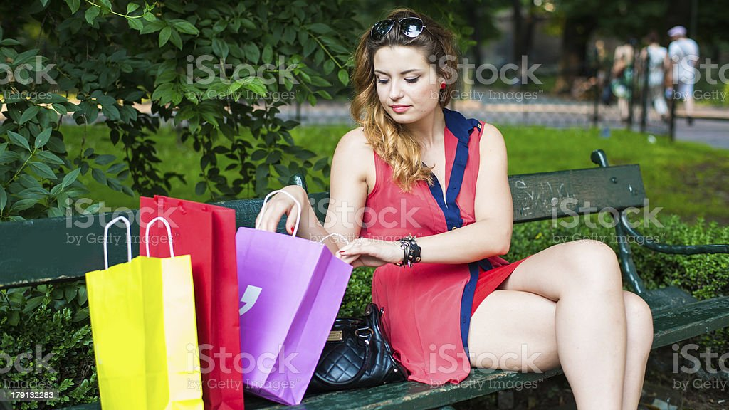 Young beautiful woman checking the shopping bags. royalty-free stock photo