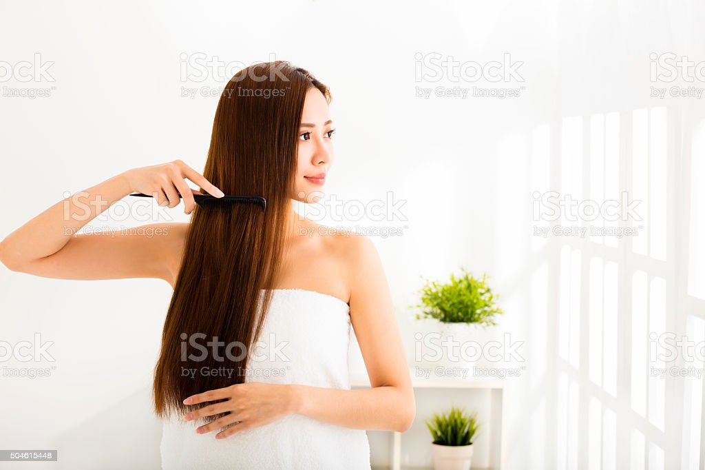 young beautiful woman combing her hair  in living room stock photo