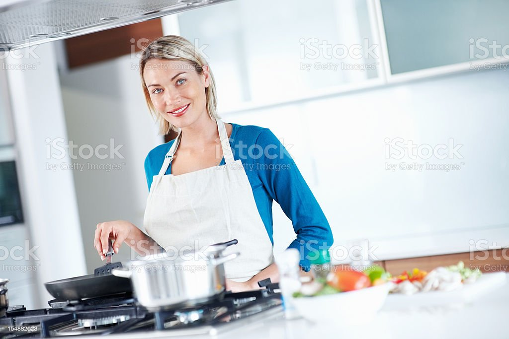Young beautiful woman cooking food in kitchen stock photo