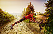 Young beautiful woman doing fitness in a park.