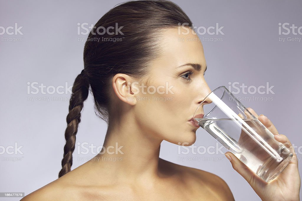 Young beautiful woman drinking a glass of mineral water royalty-free stock photo