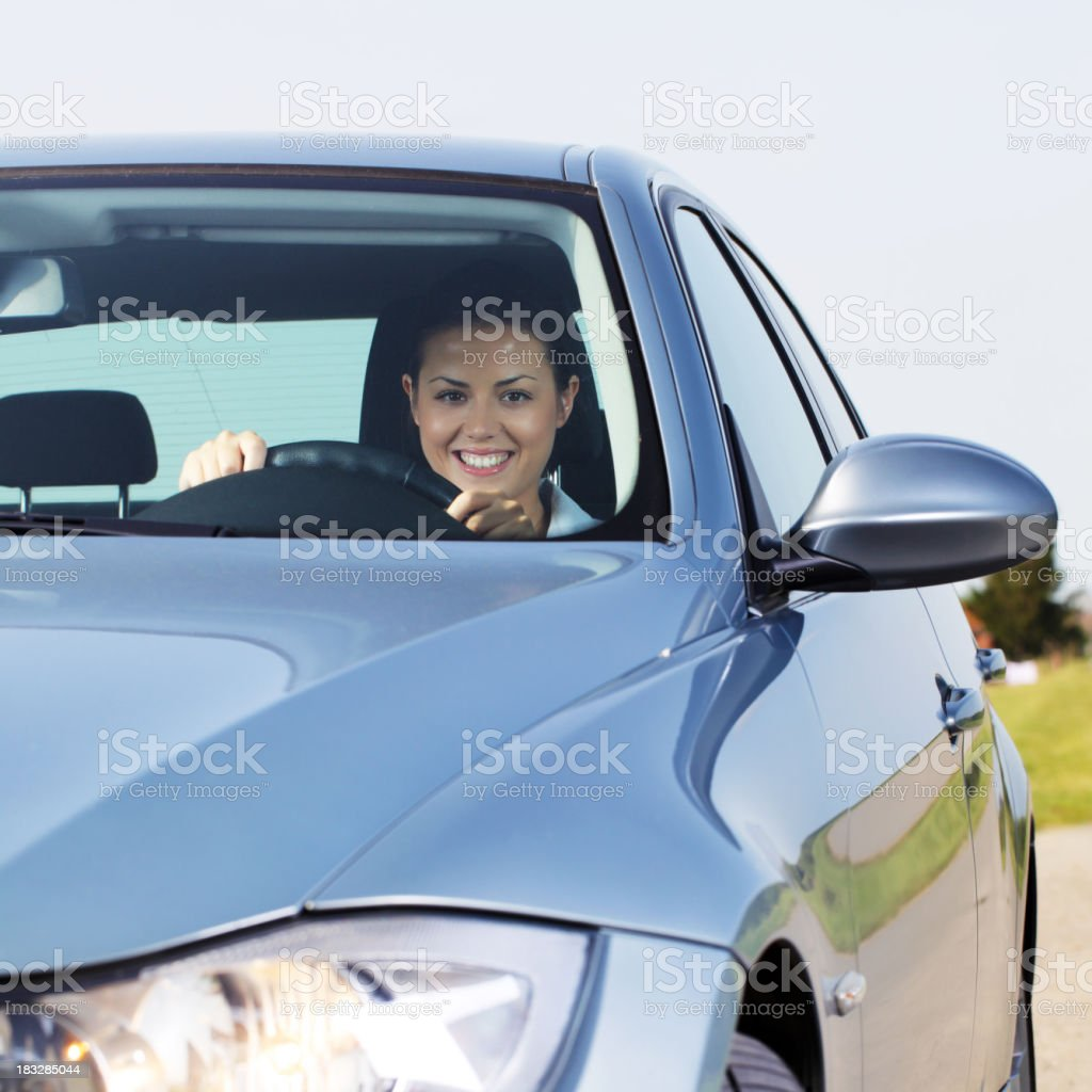 Young beautiful woman driving a car and smiling. royalty-free stock photo