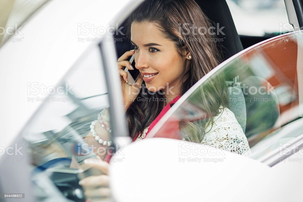 Young beautiful woman driving and talking on a cell phone stock photo