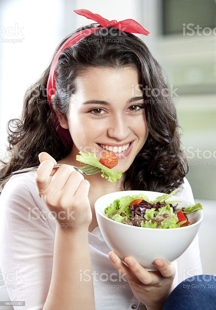 Young beautiful woman eating salad stock photo