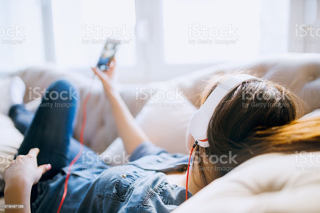 Young beautiful woman  enjoying the music at home stock photo