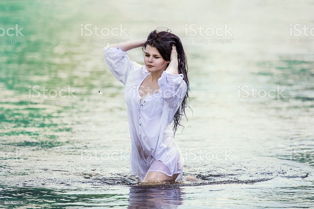 Young beautiful woman enjoys the lake with turquoise clear water stock photo