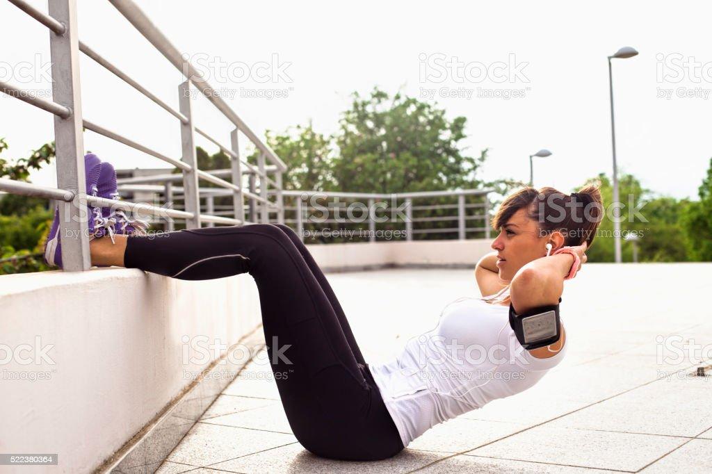 Young beautiful woman exercising outdoors stock photo
