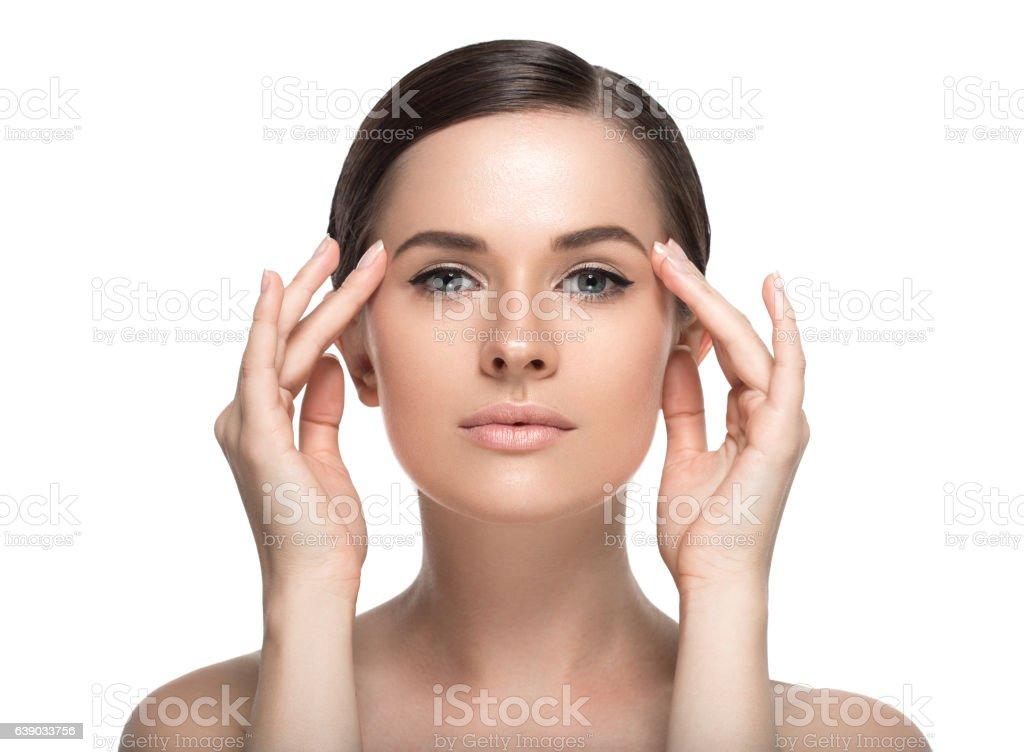 Young beautiful woman face portrait  touching her face. Studio shot. stock photo