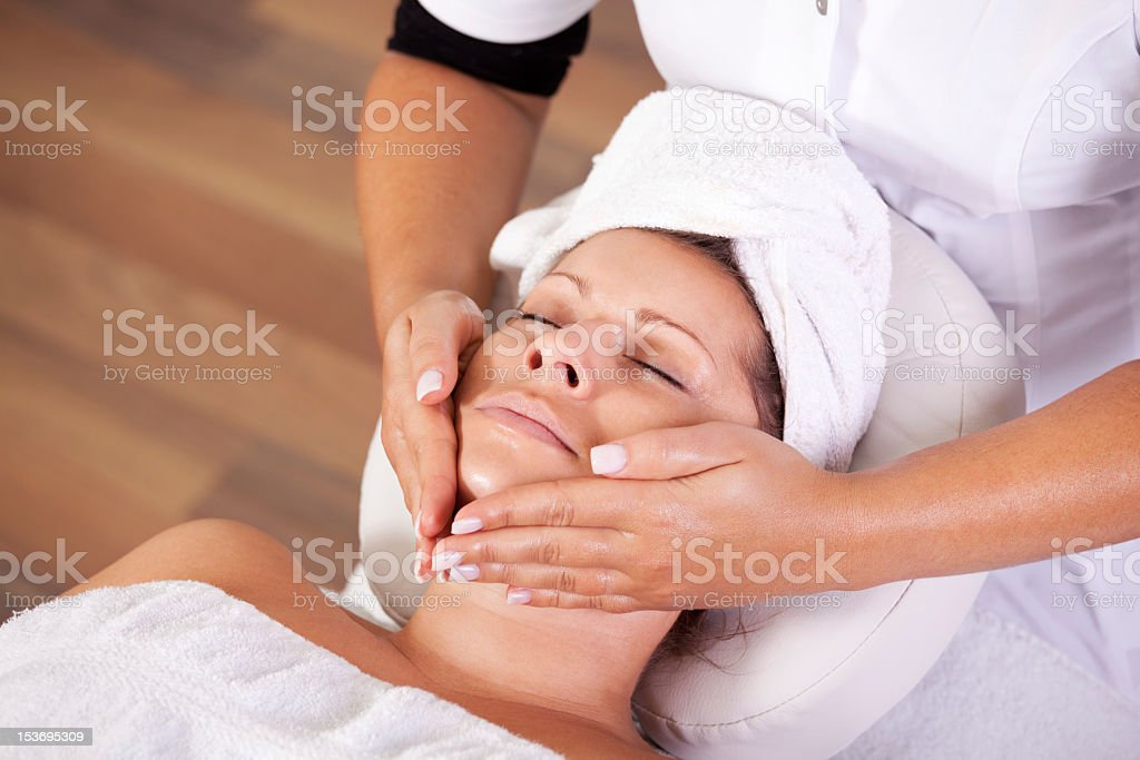 Young beautiful woman getting facial massage royalty-free stock photo