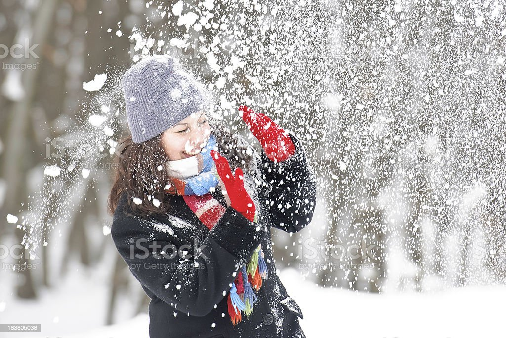 young beautiful woman getting hit by a snowball stock photo