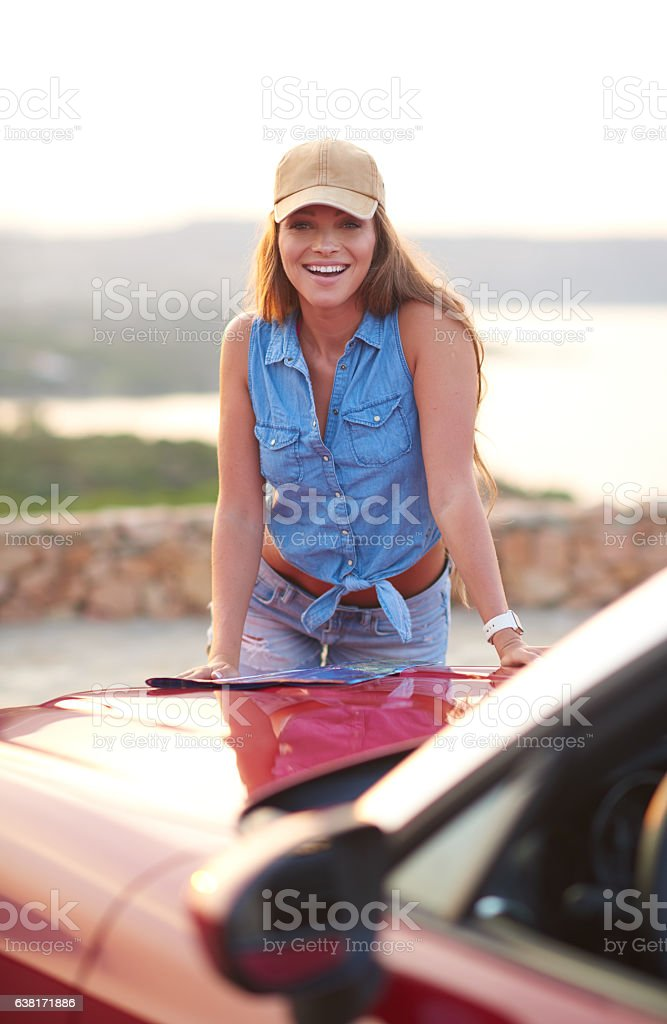 Young beautiful woman having fan on vacation with convertible car stock photo